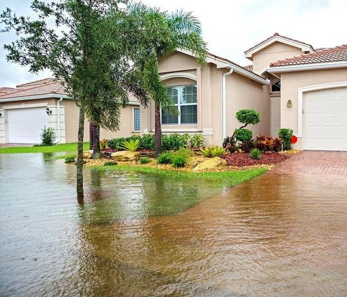 Flooding from a storm; water in yard; stucco house in background