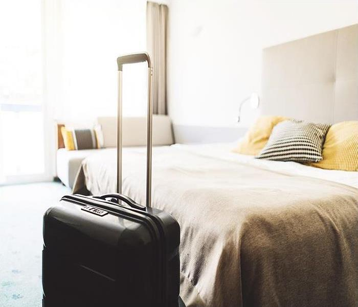 Hotel room with a suitcase at the foot of a bed