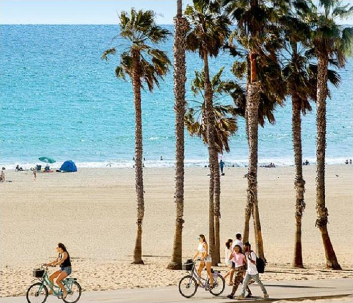 People walking and biking on sidewalk; beach and ocean in background.