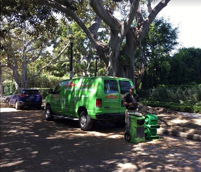SERVPRO tech with SERVPRO restoration equipment standing behind SERVPRO van parked on residential street