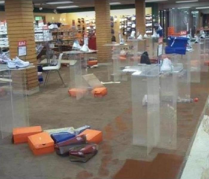 Water covering the brown floor of a shoe store