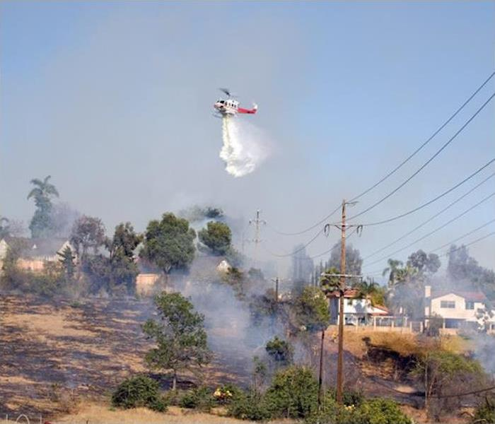 Airborne helicopter dropping water on a smoldering landscape